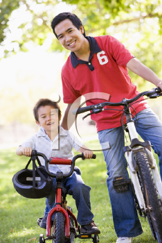 Royalty Free Photo of a Man and Boy on Bikes
