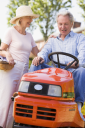 Royalty Free Photo of a Couple With a Riding Mower