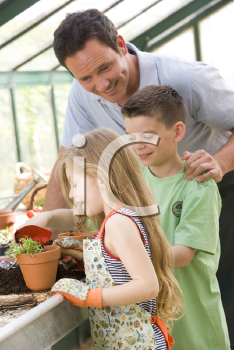 Royalty Free Photo of a Man in a Greenhouse With Children