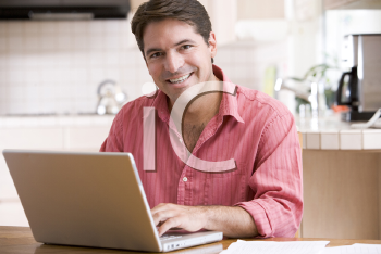 Royalty Free Photo of a Man With a Laptop in the Kitchen
