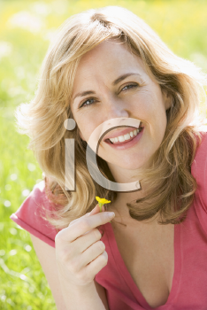 Royalty Free Photo of a Woman Holding a Buttercup