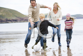 Royalty Free Photo of a Family Playing Soccer at the Beach