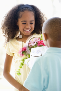 Royalty Free Photo of a Little Boy Giving a Little Girl Flowers