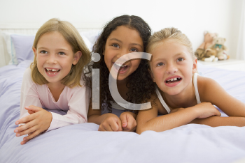 Royalty Free Photo of Three Girls Lying on a Bed in PJs