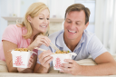 Royalty Free Photo of a Couple Eating Chinese Takeout