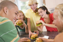 Royalty Free Photo of Teens Eating Burgers