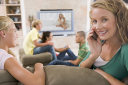 Royalty Free Photo of a Girl Talking on a Phone While Other Teens are Watching TV