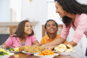 Royalty Free Photo of a Mother Serving a Meal to Her Children