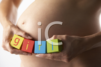 Royalty Free Photo of a Pregnant Woman Holding the Word Girl