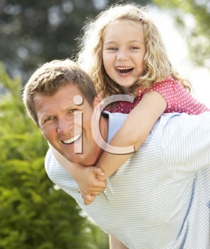 Royalty Free Photo of a Father Giving His Daughter a Piggyback Ride