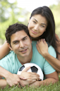 Royalty Free Photo of a Couple on the Ground With a Soccer Ball