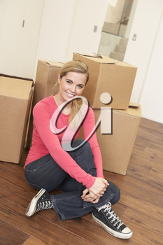 Young woman on moving day sitting on floor among cardboard boxes