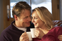 Middle Aged Couple Sitting On Sofa With Hot Drinks