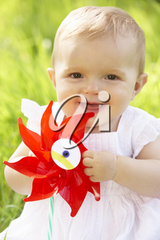 Baby Girl In Summer Dress Sitting In Field Holding Windmill