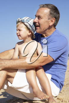 Grandfather And Grandson Sitting On Beach
