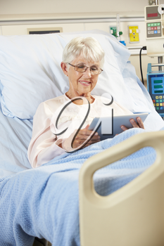 Senior Female Patient Relaxing In Hospital Bed With Digital Tablet
