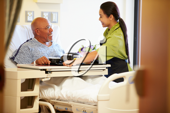 Senior Male Patient Being Served Meal In Hospital Bed