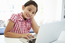 Asian Child Using Laptop At Home