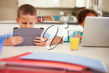 Children Using Laptop And Digital Tablet To Do Homework