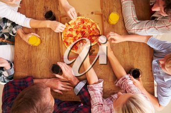 Friends sharing a pizza together, overhead view
