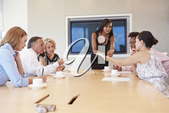 Businesswoman By Screen Addressing Boardroom Meeting