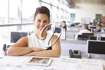Female architect at her desk, smiling to camera