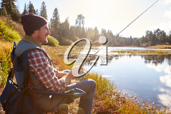 Man relaxing and fishing by lakeside, California, USA