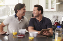 Male gay couple in kitchen with tablet looking at each other