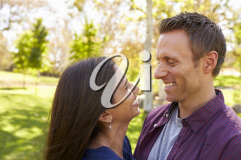 Happy mixed race couple in park look at each other, close up