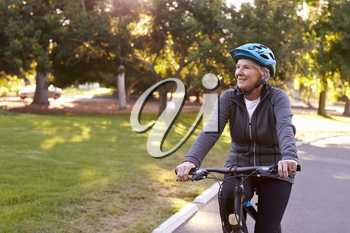 Front View Of Senior Woman Cycling Through Park