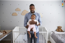 Portrait Of Father Holding Baby Daughter In Nursery