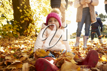 Young Girl Sitting In Leaves In Autumn Garden