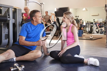 Senior Man Discussing Exercise Program With Male Personal Trainer In Gym