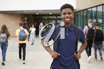 Portrait Of Smiling Male High School Student Outside College Building With Other Teenage Students In Background