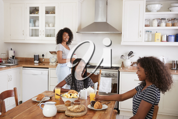 Three Teenage Girls Eating Breakfast In Kitchen Together