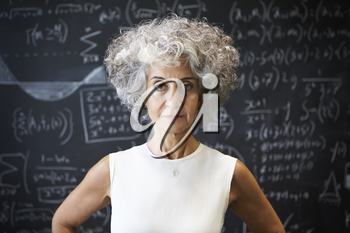 Middle aged academic woman standing in front of blackboard