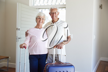 Portrait Of Senior Couple Arriving At Summer Vacation Rental