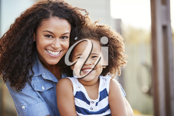 Mixed race mother and young daughter smile to camera outside
