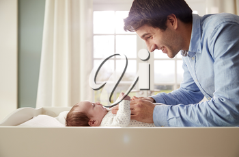 Father Playing With Newborn Baby Lying On Changing Table