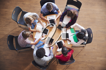 Overhead Shot Of High School Pupils Using Digital Tablets In Group Study Around Tables