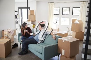 Happy Couple Resting On Sofa Surrounded By Boxes In New Home On Moving Day