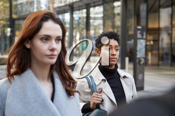 Two young adult businesswomen walking in the city of London, close up, selective focus