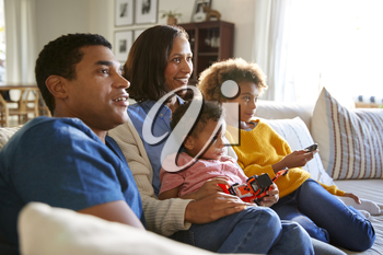 Young family sitting together on the sofa in their living room watching TV, selective focus