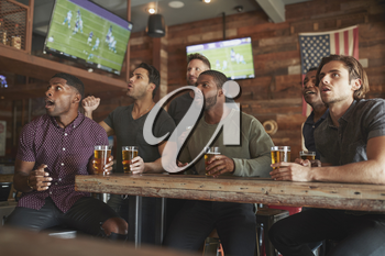 Group Of Male Friends Watching Game On Screen In Sports Bar