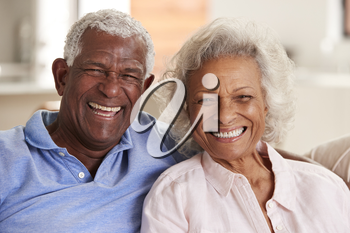 Portrait Of Loving Senior Couple Sitting On Sofa At Home Together