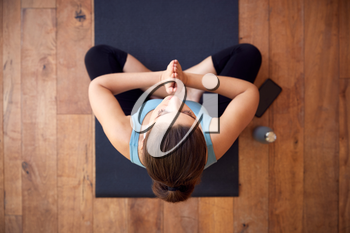 Overhead View Of Woman Sitting On Exercise Mat Wearing Wireless Earphones Connected To Mobile Phone