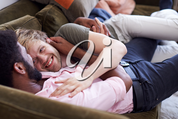 Loving Male Gay Couple Relaxing Lying On Sofa At Home Hugging