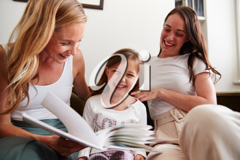 Same Sex Female Couple Reading Book With Daughter At Home Together Whilst Tickling Her