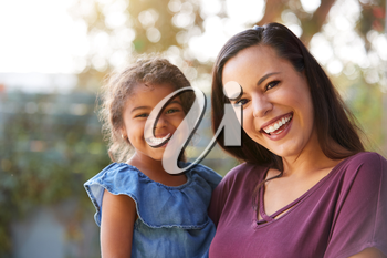 Portrait Of Smiling Hispanic Mother With Daughter Laughing In Garden At Home