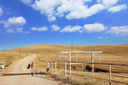 Unpaved country road in the desert with a fence for the cows.